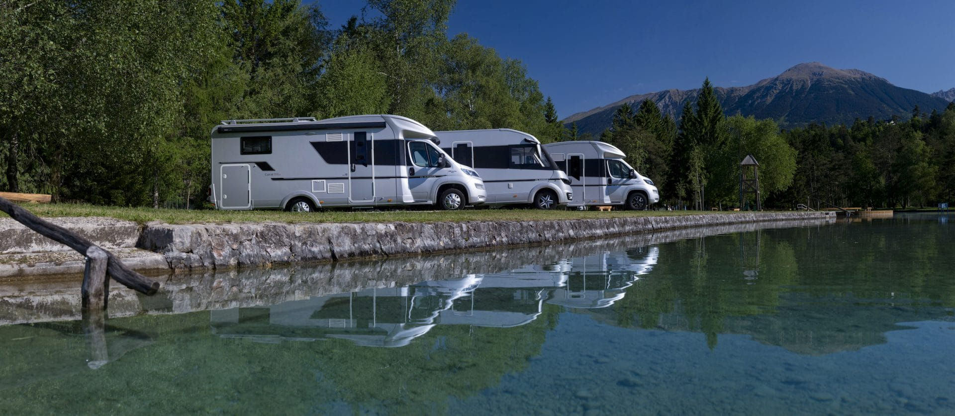 drei Wohnmobile an einem glatten Gewässer