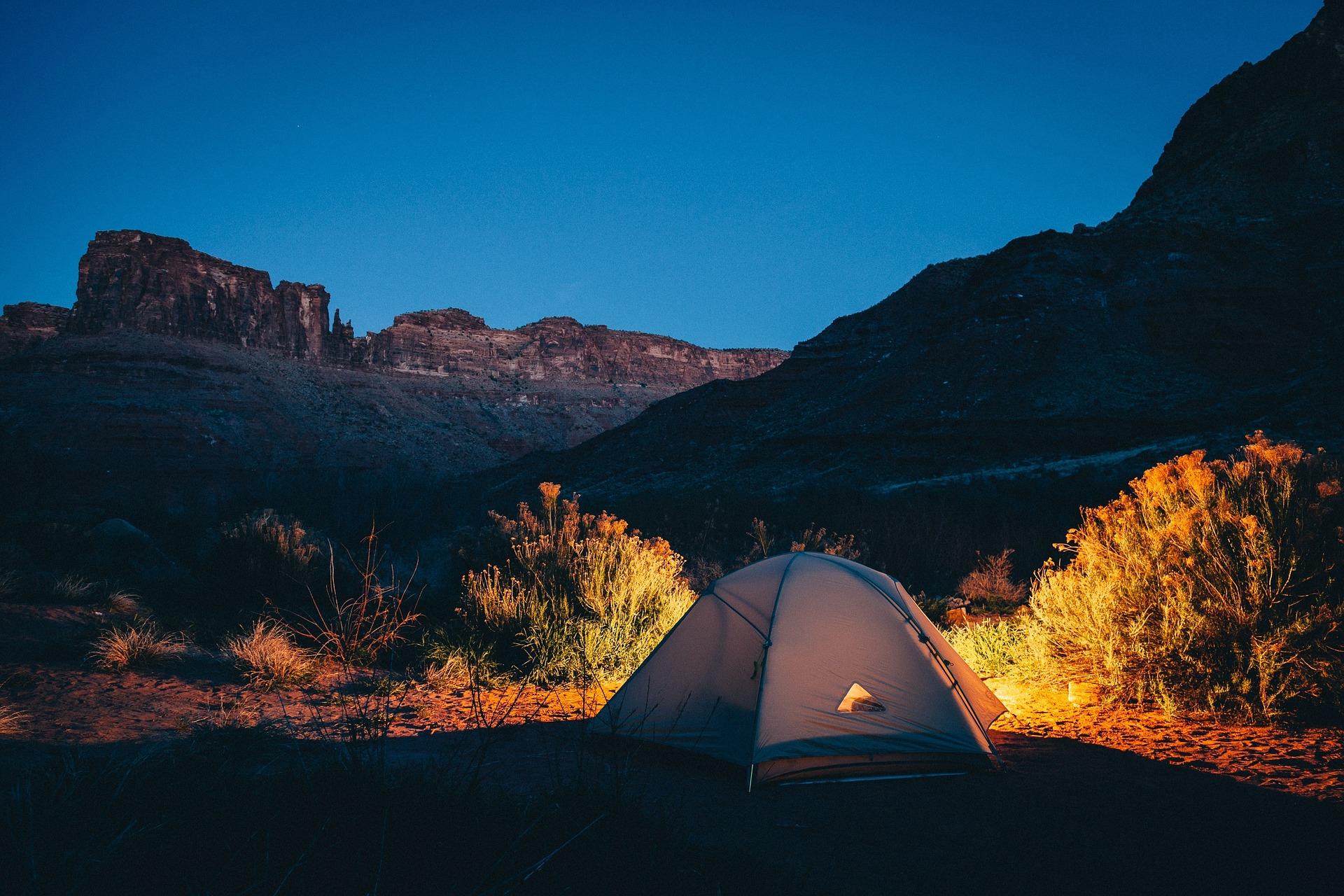 Beleuchtetes Zelt vor Hügelkette in der Nacht