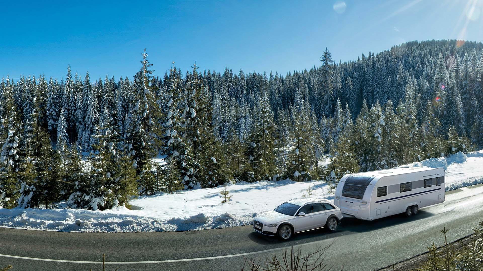Adria Alpina-Wohnwagen in bezaubernder Winterlandschaft, gezogen von einem weißen SUV